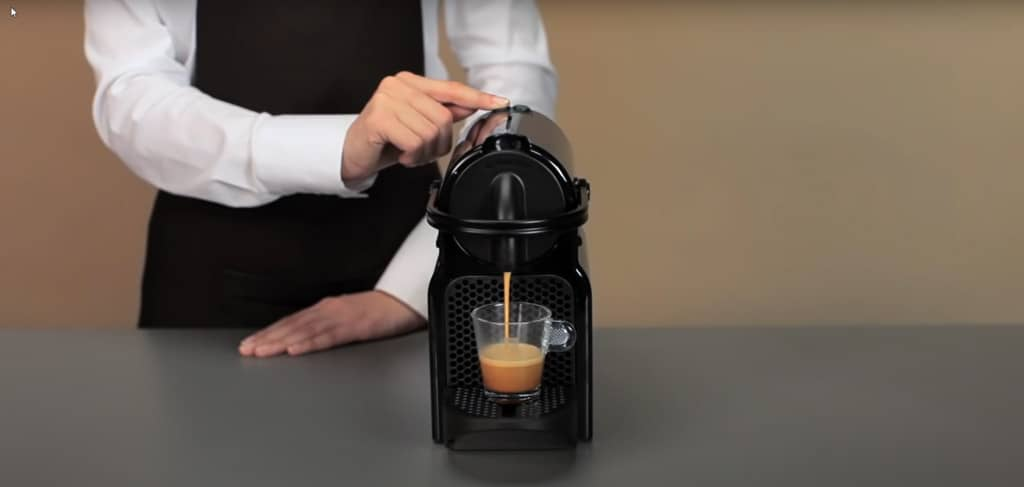 lady demonstrates how to factory reset a nespresso machine